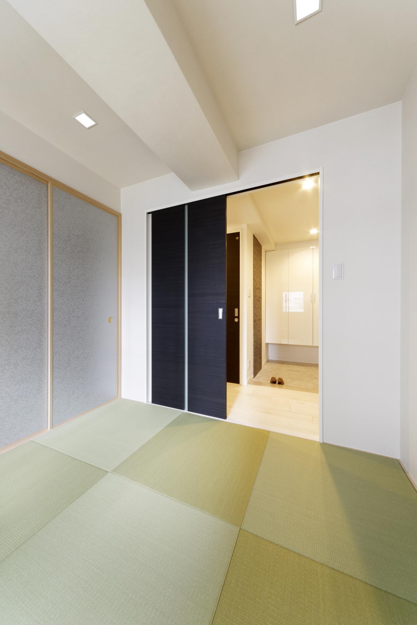 玄関横に新たに設けた和室。照明はダウンライトにして天井をすっきりさせた。押入れの並びに仏間を設けている。