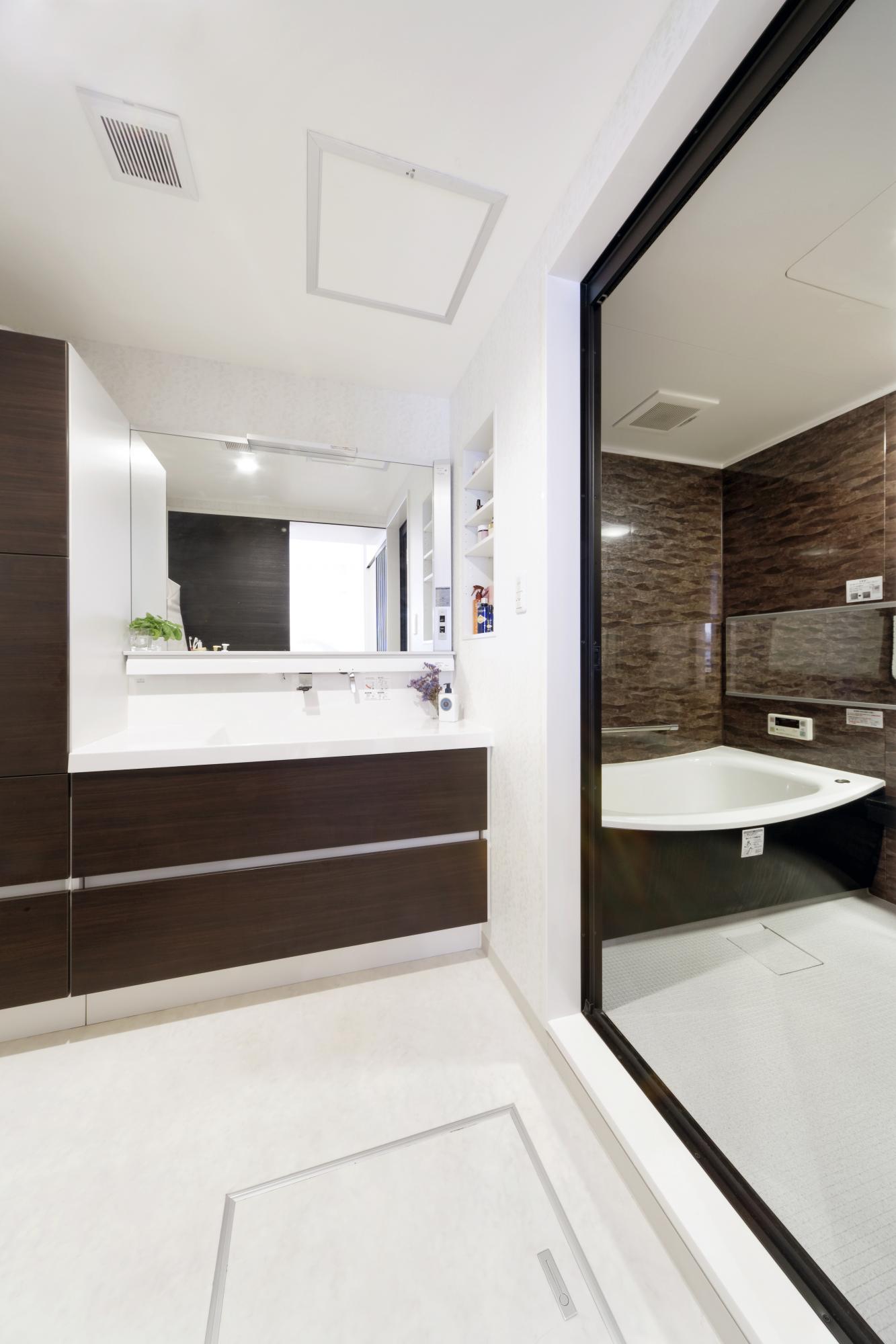 キッチンのカップボードと色や質感を合わせた洗面化粧台。浴室も大理石調の落ち着いたデザインの物を選んだ。浴槽もゆとりのあるサイズを選択。