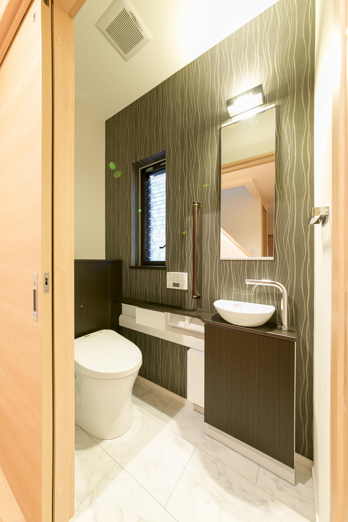 1階のトイレ入り口を引き戸にして使いやすさに配慮。新たに手洗いスペースも設けた。