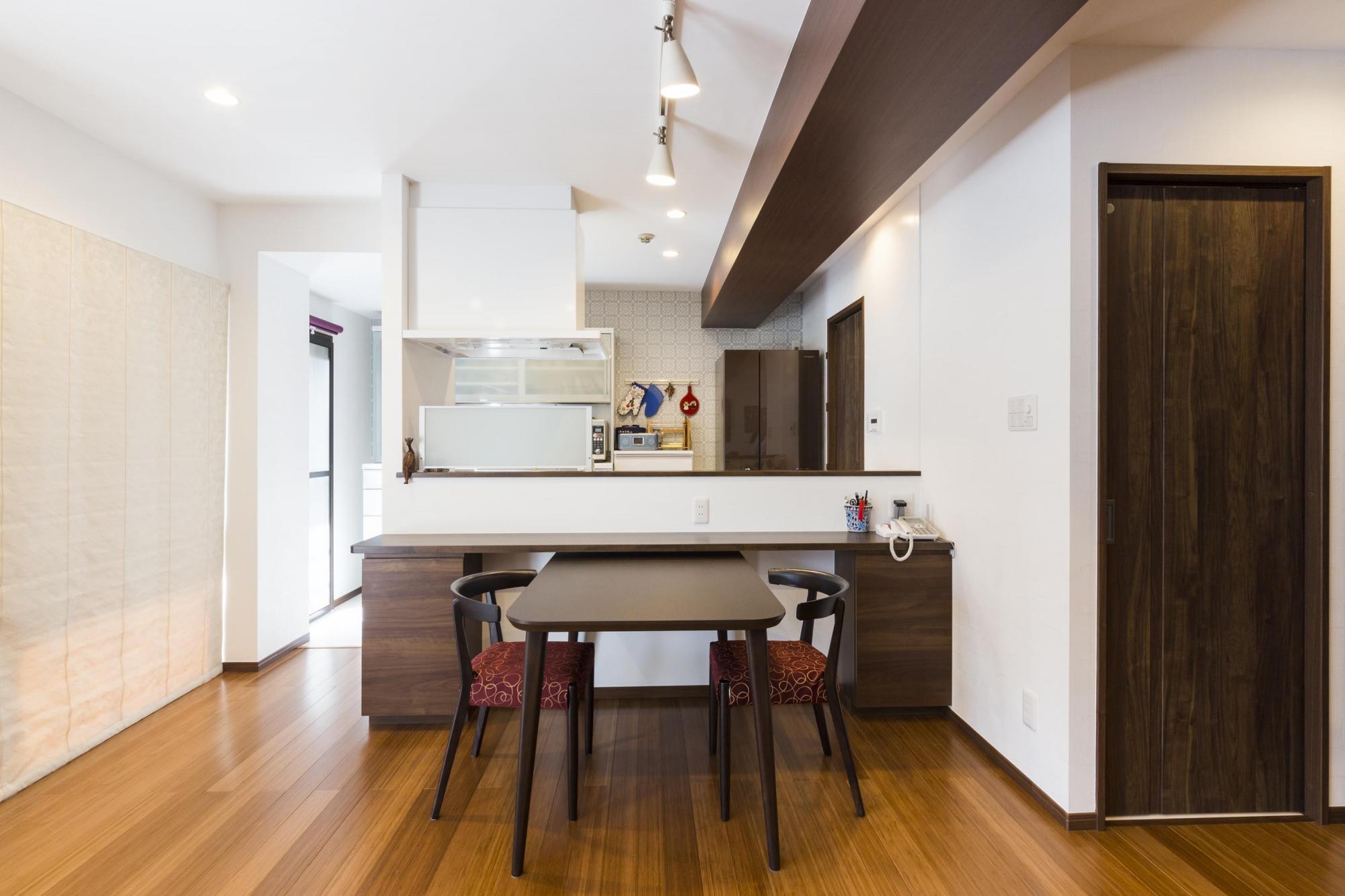 壁付けだったキッチンを対面式にしてカウンターも設けた。キッチンの手元は隠しているので、片付けに気を使うこともない。正面に見えるカップボード後ろの壁はアクセントクロスにして、インテリアに変化をつけた。