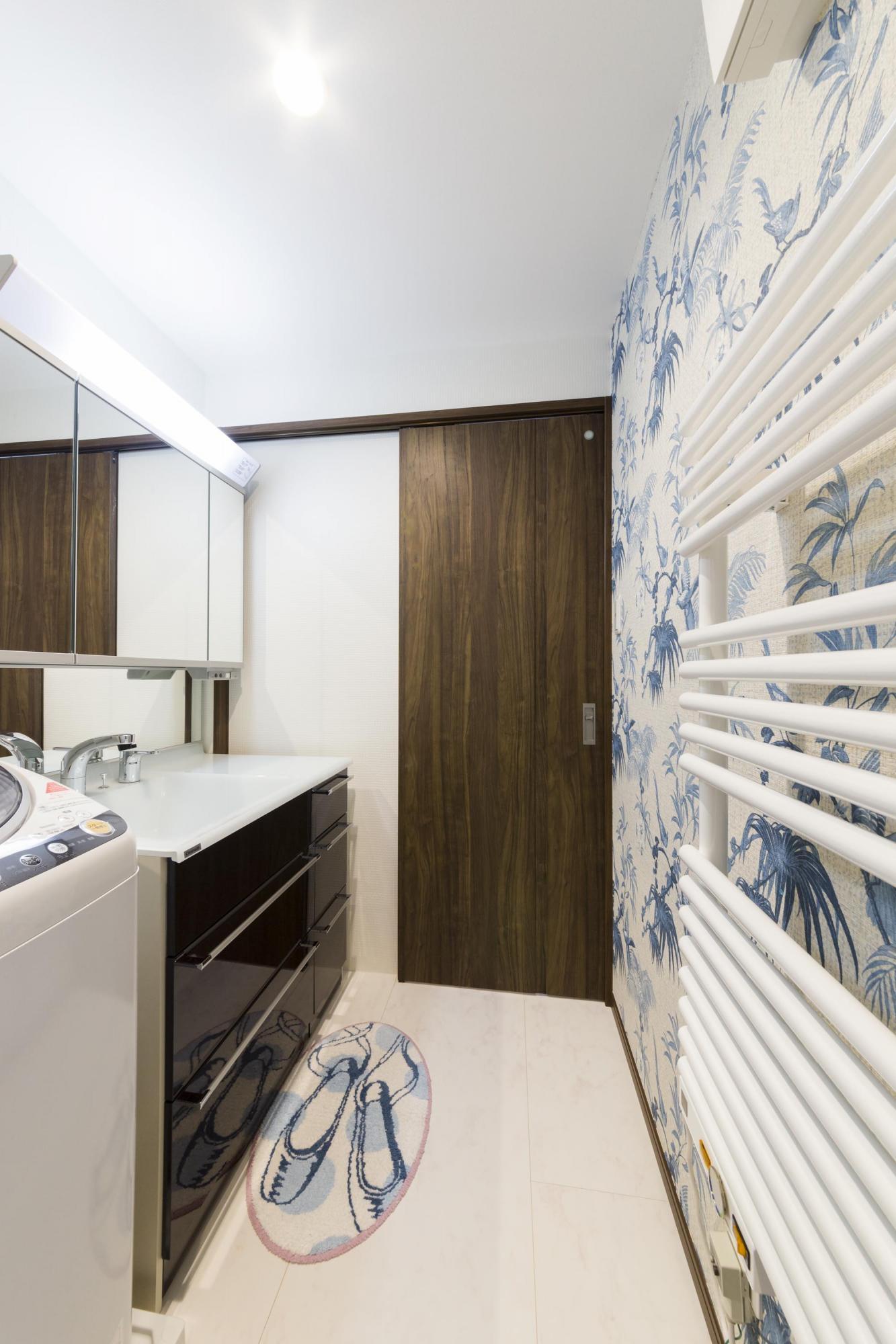 洗面空間にもアクセントクロスを使って明るく楽しげなイメージに仕上げた。お洒落なデザインのタオルウォーマーも備えている。