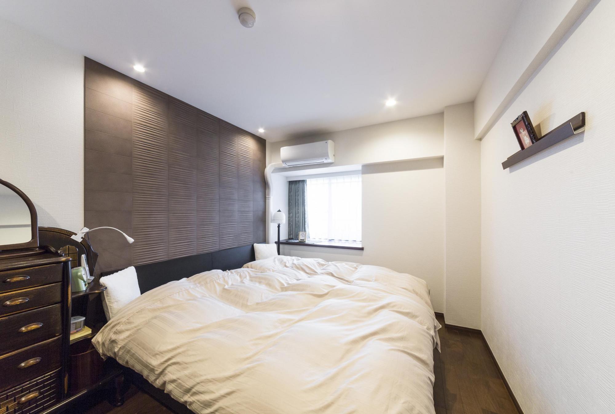 従来の和室のスペースを使って広くした寝室。エコカラットを大胆に使い、ダウンライトで質感を強調した。