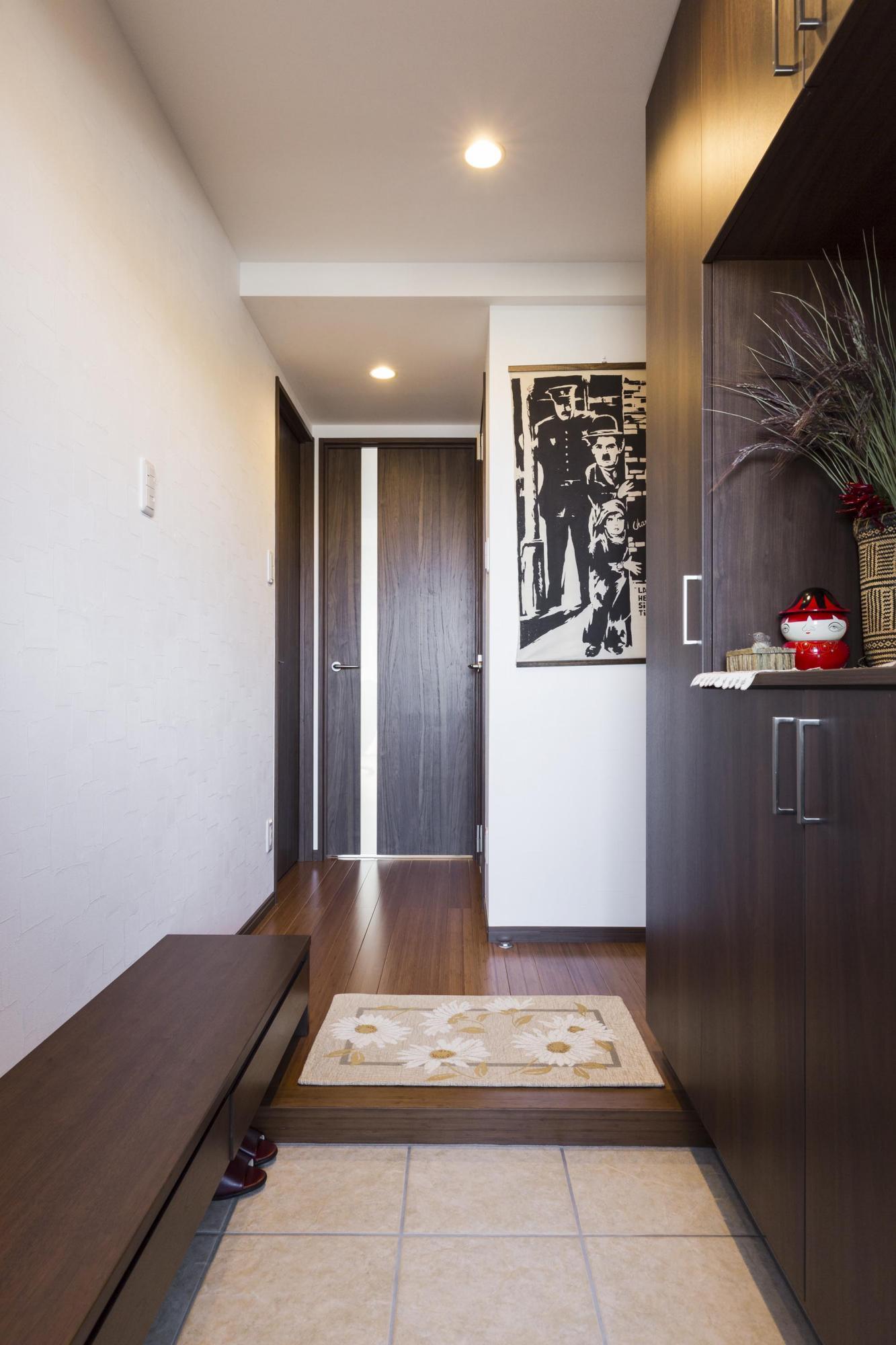 玄関は収納家具を新しくしたほか、同じ素材でベンチを製作した。