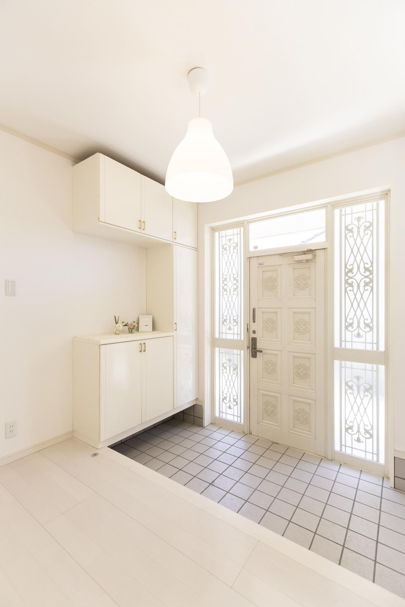 1階玄関もインテリアに合わせ白を基調にリフォーム。アイアンを組み込んだ両袖のガラスが、光を導くとともにエレガントな雰囲気をつくる