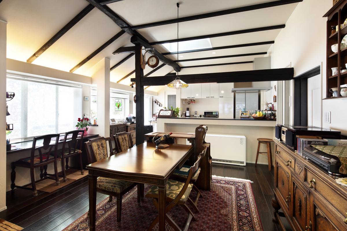 白壁と黒い梁と柱のコントラストが印象的な室内。家具や調度品の英国アンティークのテイストとマッチした、シンプルで和モダンなイメージに
