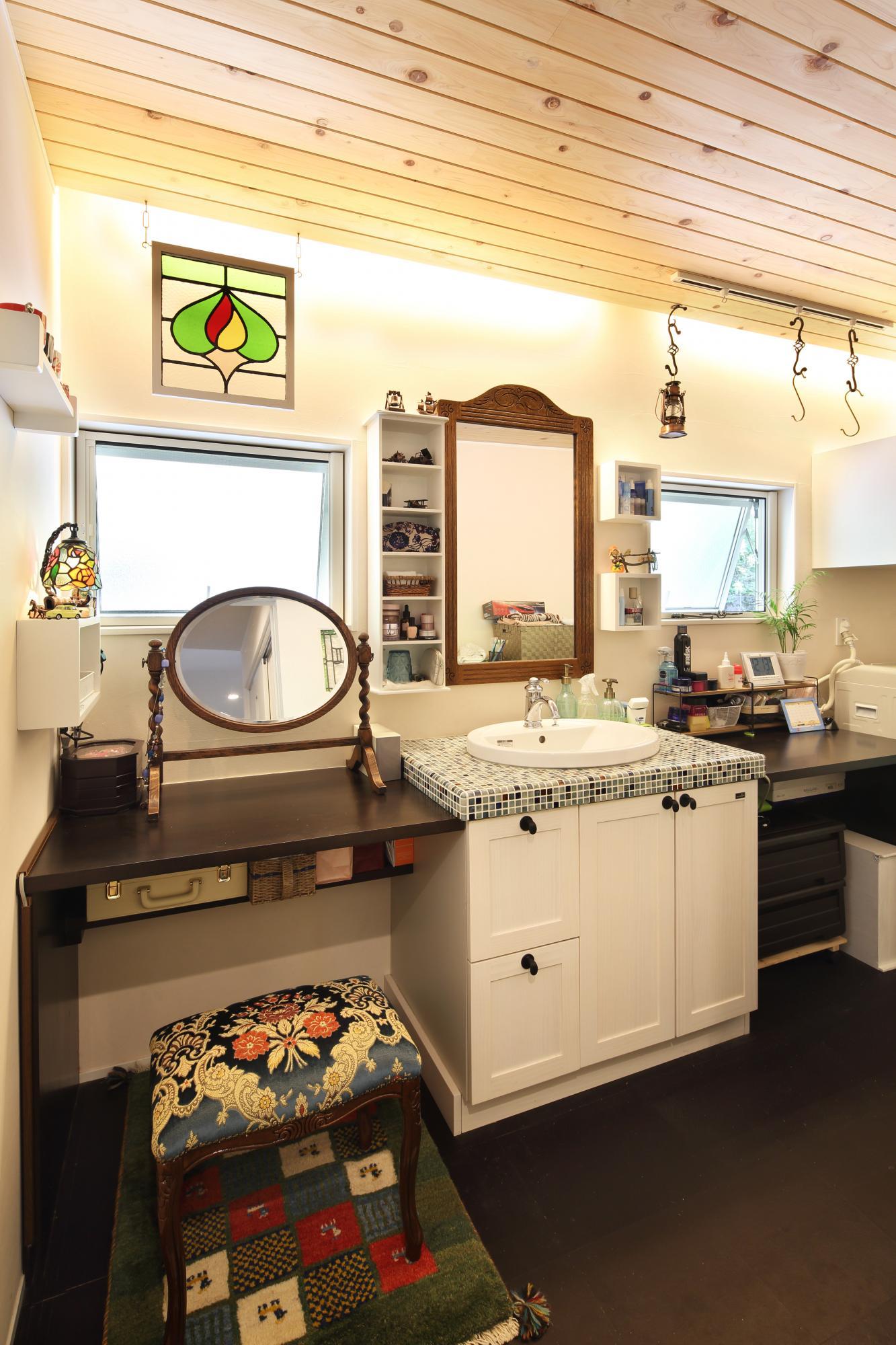 タイル貼りの天板、板張りの天井に間接照明が温もりを与えるアンティーク調の洗面室。使い勝手にも配慮し十分なスペースを確保