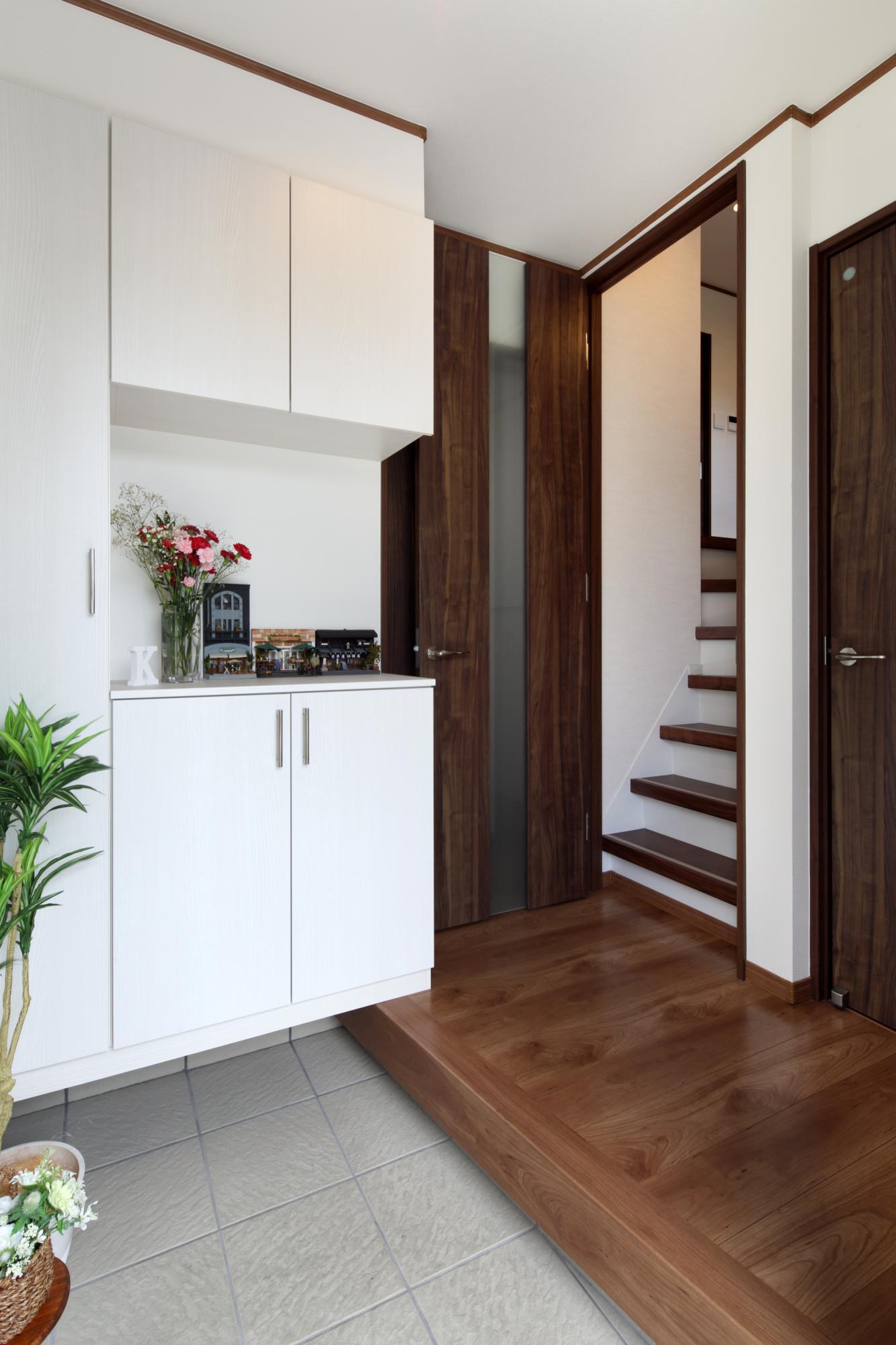 玄関にはシューズクロークなどの収納スペースを造作して片づけもスムーズ。 白を基調に家具類はダーク系で統一されています