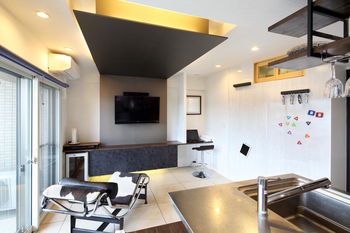 壁の一部をマグネットボードにしてお子様が遊べるような工夫も施しました。壁掛け式のテレビの横にはパソコンコーナーを造作。下がり天井に間接照明の演出もおしゃれ