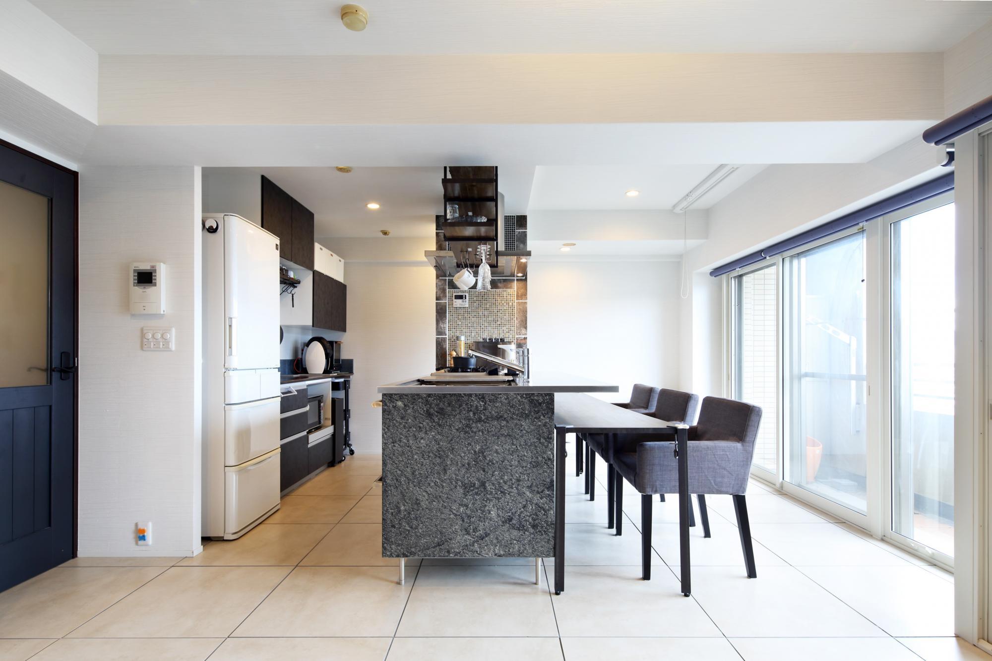 コミュニケーションと家事動線を重視してアイランドキッチンを配したLDK。床は600角のタイルを採用し、モノトーンコーディネイトのモダンな住空間に