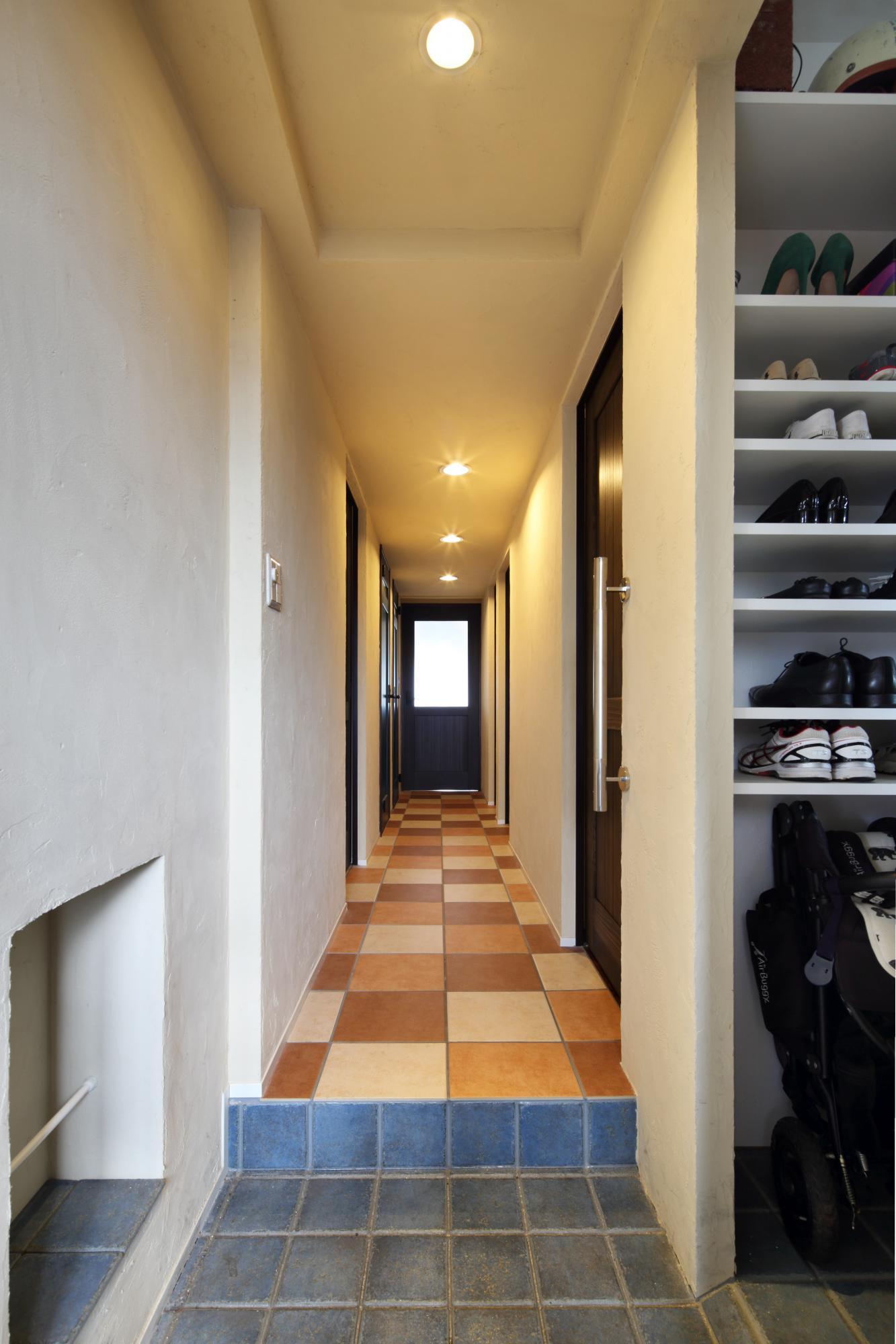 珪藻土の壁、テラコッタの床で暖かい印象のコリドー。扉を一段奥に取付けるため壁を厚くし、それぞれの部屋が異なる印象であることを強調しました