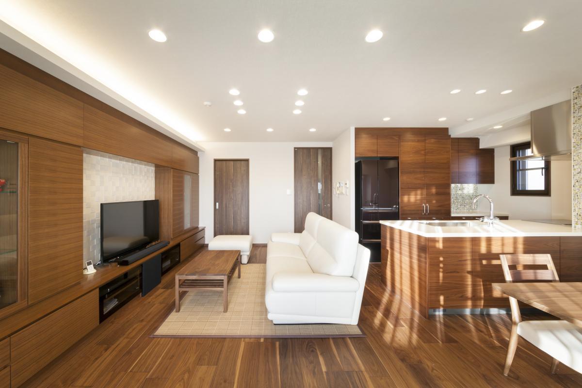 吊戸があり開口部が小さく閉鎖的だったキッチンは、オープンにして明るく開放的に。TVボードを兼ねる大容量の壁面収納の効果で、いつでもスッキリとした空間を実現。キッチンの熱源設備はIHで火の心配もなくなり、床暖房や照明の調光機能なども導入しています