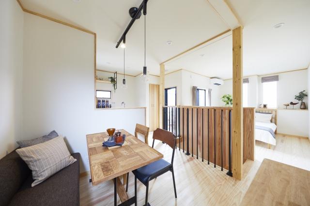 階段を上がって右手がリビング・キッチン、左手が寝室となります。間仕切りの扉は設けず、同じ空間でありながら階段手すりによって視覚的にスペースを分けています。